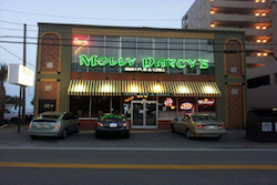 molly darcy's exterior with green neon lights and cars parked infront, pet friendly restaurant in Myrtle Beach, SC