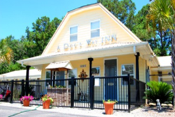 a dog's way inn exterior, yellow 2 story building with black fence and gate, daycare in myrtle beach