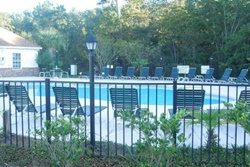 pool with lounge chairs all around and fencing, pet friendly vacation rental in myrtle beach