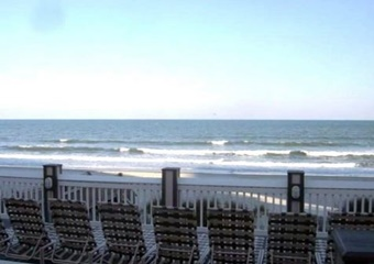 oceanfront deck and lounge area wth white railing and sun chairs, myrtle beach pet friendly vacation rental home