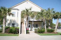 front of a yellow/off-white 2 story house with landscaping and palm trees in the front, pet friendly vacation rental in myrtle beach